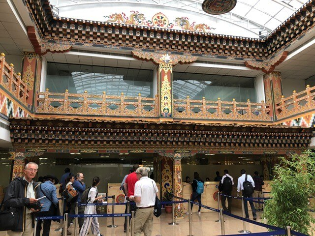 Bhutan: Landet af torden Dragon Rita payne Brutto national lykke Kongen af Himalaya-kongeriget Bhutan skabte internationale overskrifter, da han erklærede, at grov national lykke er regeringens mål, og at økonomien ikke skal betragtes som den eneste måling af succes.  Den nuværende konge har ligesom sine forfædre stræbt efter at opretholde en balance mellem fremskridt og udvikling og samtidig bevare kongedømmets unikke kultur og arv.  Bhutans charme, hvis oprindelige navn, Druk Yul, betyder Thunder Dragon's Land, bliver tydelig, når man flyver ind i kongeriget.  Flyet ned gennem skyerne over spektakulære bjerglandskaber for at lande i Paro lufthavn.  I modsætning til de fleste kedelige og standard internationale terminaler er strukturen og designet baseret på bhutanske stilarter med udskårne trætag og søjler og buddhistiske tema vægmalerier på væggene.  Tashi Namgay Resort, som var vores vigtigste base under vores ophold, ligger bekvemt overfor lufthavnen.  Som de fleste andre bygninger i Bhutan henter hotelkomplekset også inspiration fra traditionel lokal arkitektur, mens det leverer alle de bekvemmeligheder, der forventes på et luksuriøst sted.  Tiger's Nest og andre attraktioner Paro betragtes som en af de smukkeste af Bhutans dale.  Vi vågnede den første fulde dag af vores besøg til lyden af den hurtigtstrømmende flod, der løber langs bunden af hotelforbindelsen fra dens kilde i Himalaya-bjergene.  Vi blev mødt af vores guide, Namgay, og den unge chauffør, Benjoy, som blev vores betroede og informerede ledsagere under hele vores besøg.  Den første ting på vores program var muligvis den mest udfordrende.  Vores mål var at klatre til Paro Taktsang-klosteret, populært kendt som Tiger's Nest, der klæber usikkert til kanten af en stejl klippe.  Desværre måtte jeg give op, da vi var mindre end en fjerdedel af vejen op, og måtte acceptere, at jeg simpelthen ikke var fit nok til at gennemføre trek.  Min mand, der er lavet af strengere ting, var med rette stolt af at kla