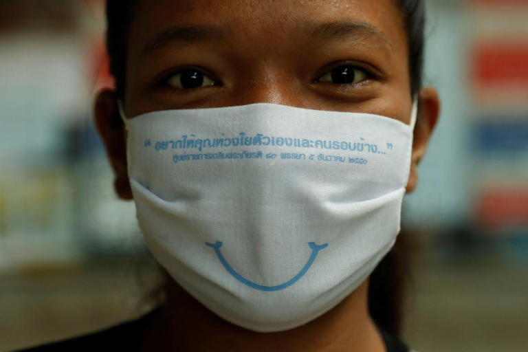 Amazing Thailand welcomes visitors with a beautiful smile behind a face-mask