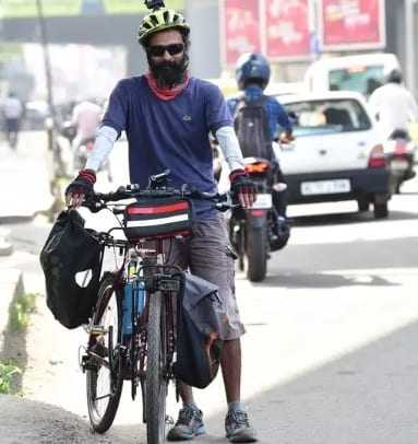 The world is full of goodness for Arun, a tourist on a bicycle